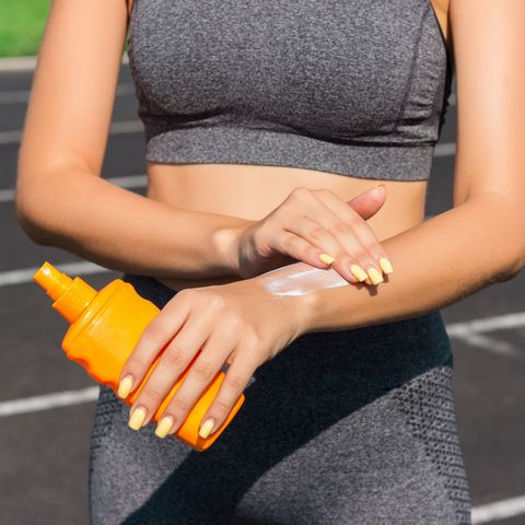 Woman spraying sunscreen cream on skin before run. Sports and healthy concept