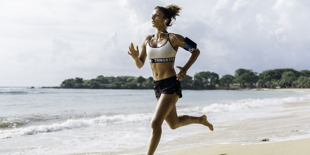 woman sprinting along beach with smart phone