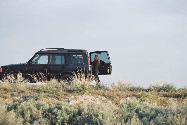 a woman standing by the open rear door of a 4x4 in open space