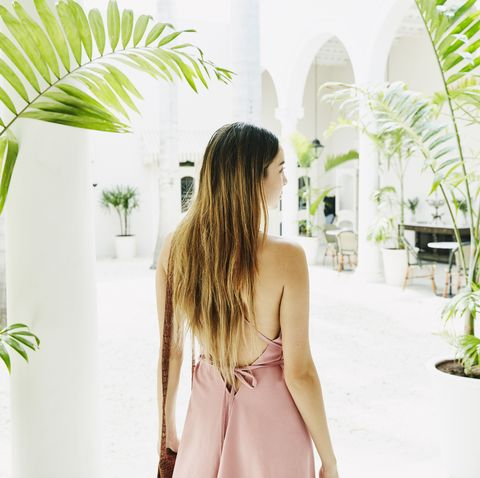 woman standing in courtyard of luxury shopping boutique