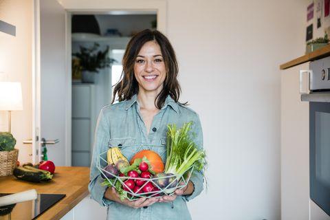 una mujer sostiene una cesta de frutas y verduras en el interior de una cocina
