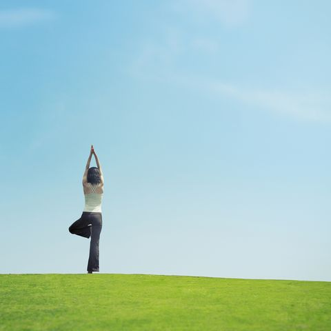 woman standing in tree pose  on lawn