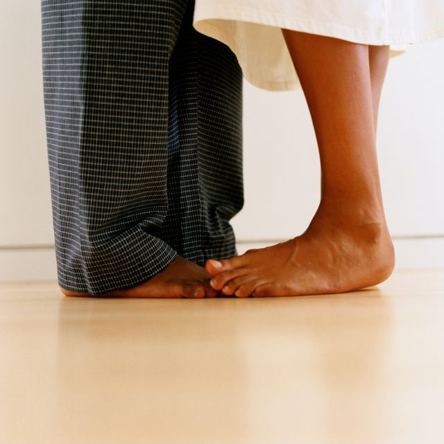 woman standing on man's feet barefoot, ground view