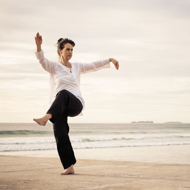 woman standing poised practicing wu tai chi on the end of a concrete pier sunset behind