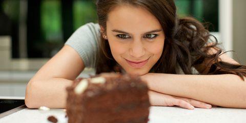 Woman staring at chocolate cake