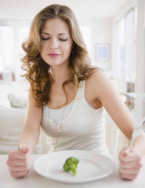woman staring at piece of brocolli on plate