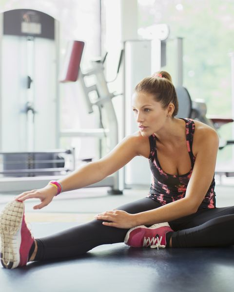 Woman stretching leg at gym