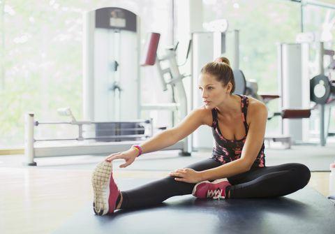 Woman stretching leg at gym