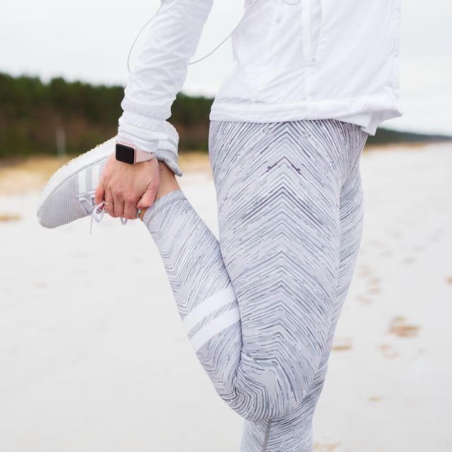 woman stretching leg before run