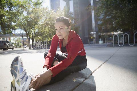 Woman stretching leg on sunny urban sidewalk