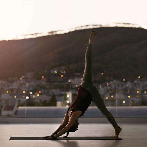 Woman stretching on yoga mat, at sunset