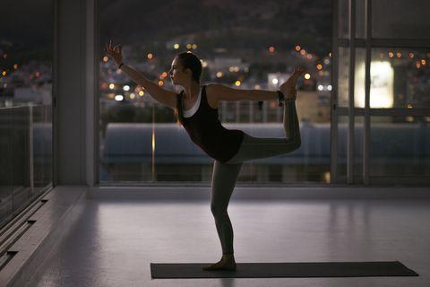 woman stretching onone leg on yoga mat, at sunset