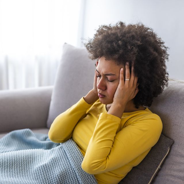 woman suffering headache sitting on a sofa in the living room at home