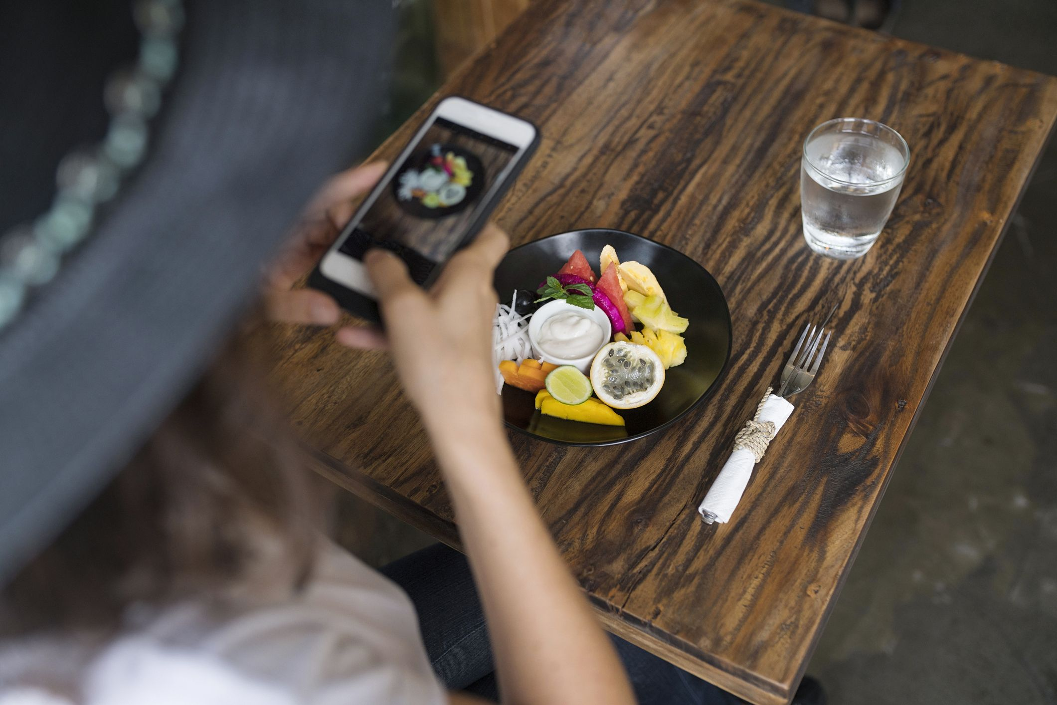 Woman taking a picture of food on a plate with smartphone