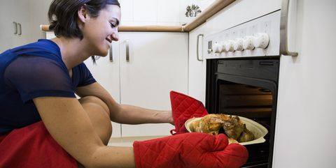 Woman taking a roast chicken from the oven