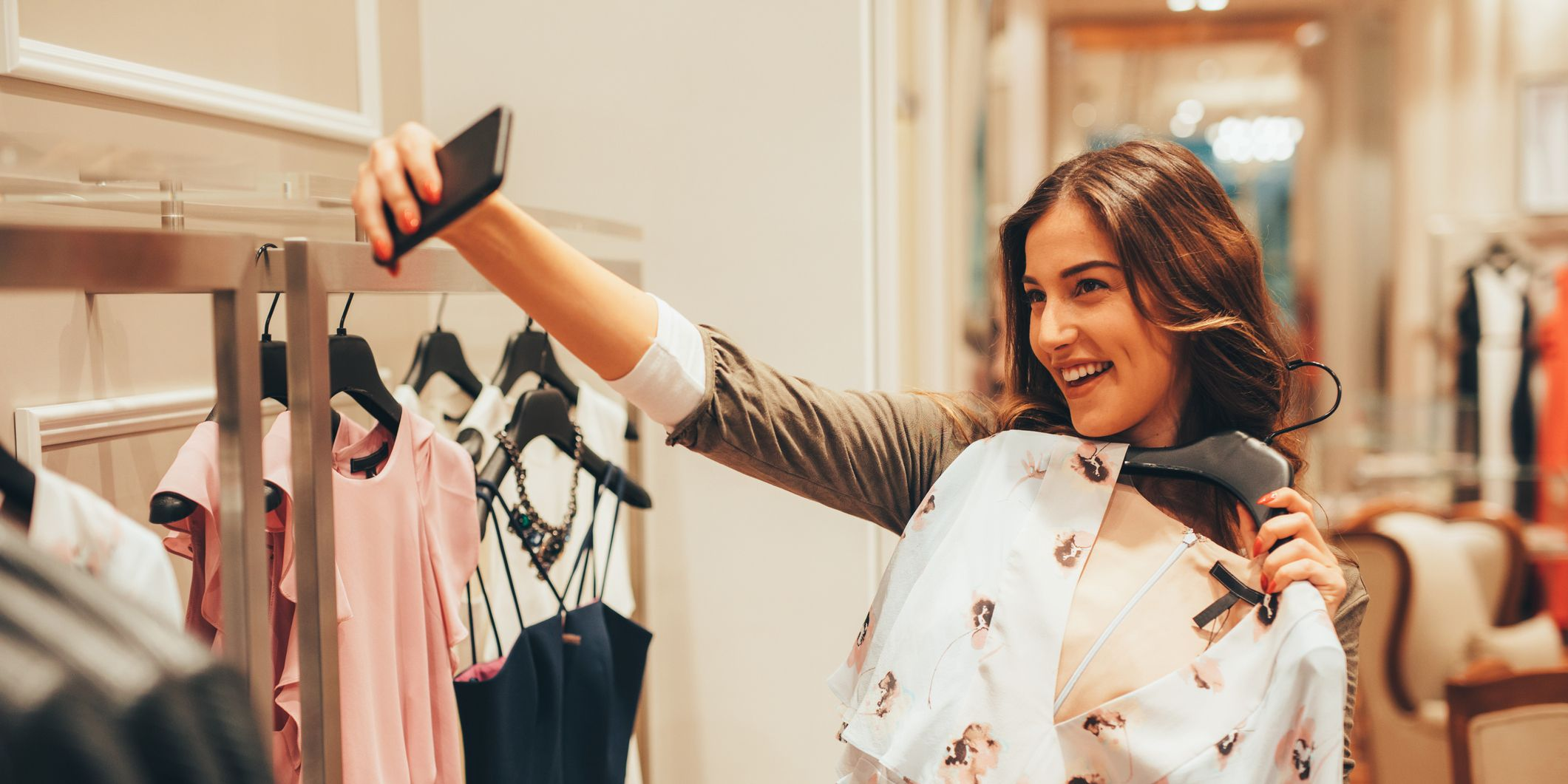 Woman taking a selfie with a blouse in a clothing store