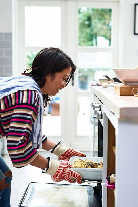 woman taking home baked meal out of oven
