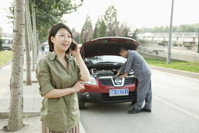woman talking on phone while mechanic fixes her car