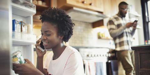 Woman talking on smart phone, reading label on jar in refrigerator in kitchen