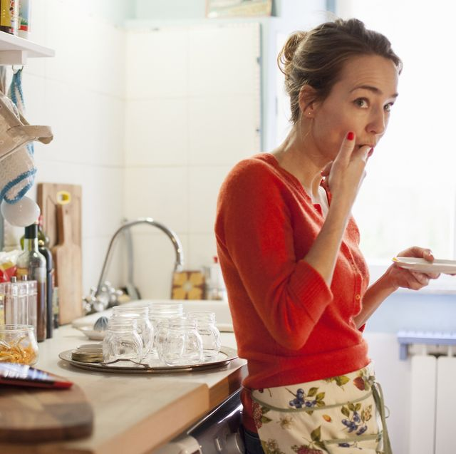 woman tasting freshly made marmalade from saucer