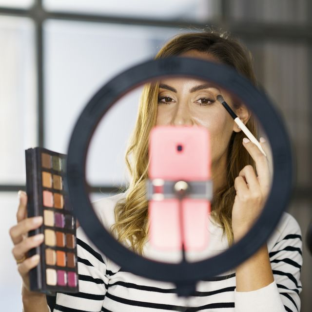 woman teaching make up on video call while sitting at home