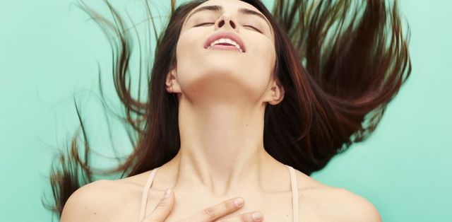 woman throwing head back in ecstasy