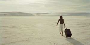Woman toting luggage across desert, rear view