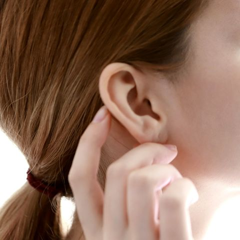 woman touching ear, close up