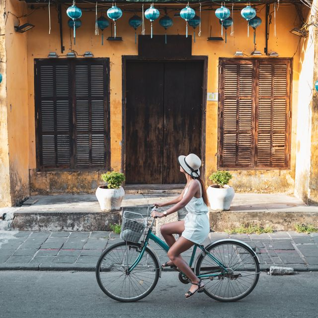 Woman tourist cycling in the old district of Hoi An in Vietnam during day .