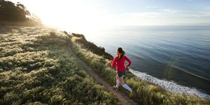Woman trail running near the ocean.