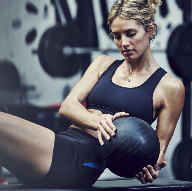 Mujer entrenando con balón medicinal en el gimnasio