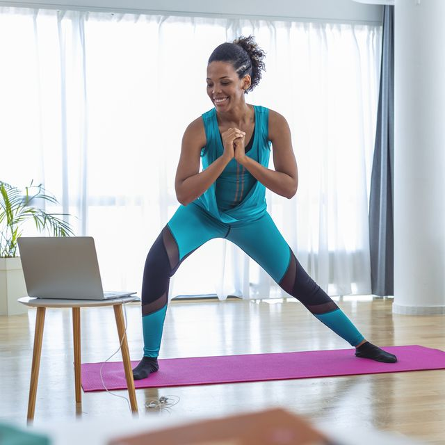 woman training indoors doing side lunges working out legs, hips and buttocks