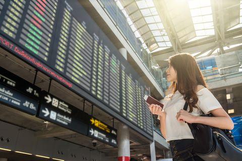 Woman holding passport at the flight information screen in modern an airport