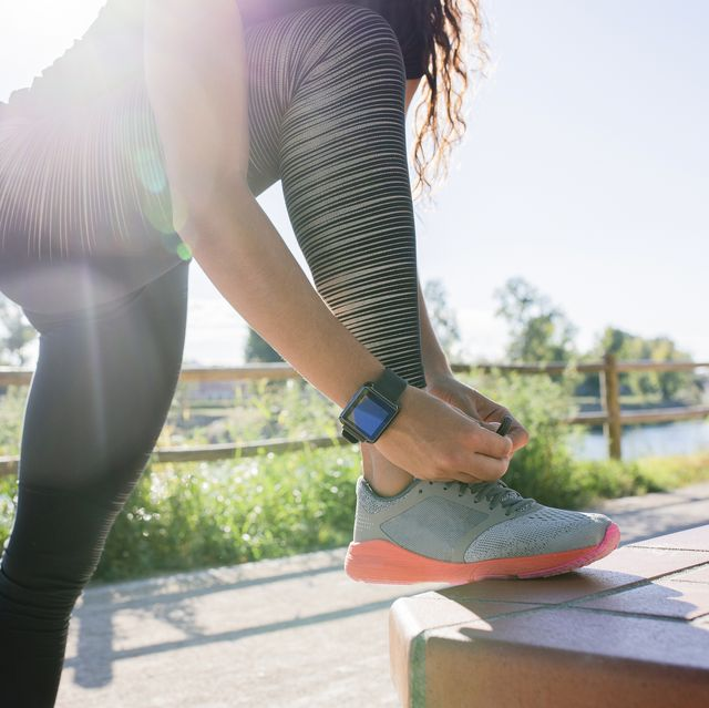 woman tying her shoe before workout