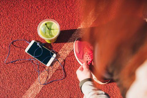 Woman tying shoelaces on stadium