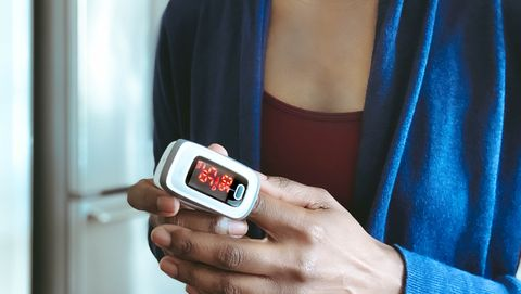 woman uses pulse oximeter