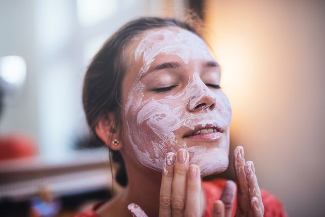 mujer usando crema solar