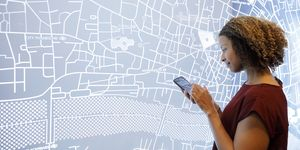 Woman using a smartphone, next to a futuristic digitally generated display