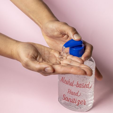 woman using alcohol based hand sanitizer