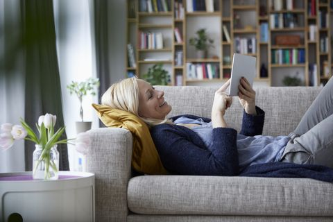 Woman using digital tablet, relaxing on couch