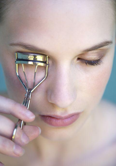 Woman using eyelash curler, close-up
