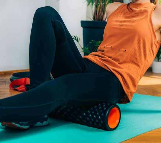 woman using foam roller to self massage muscles at home