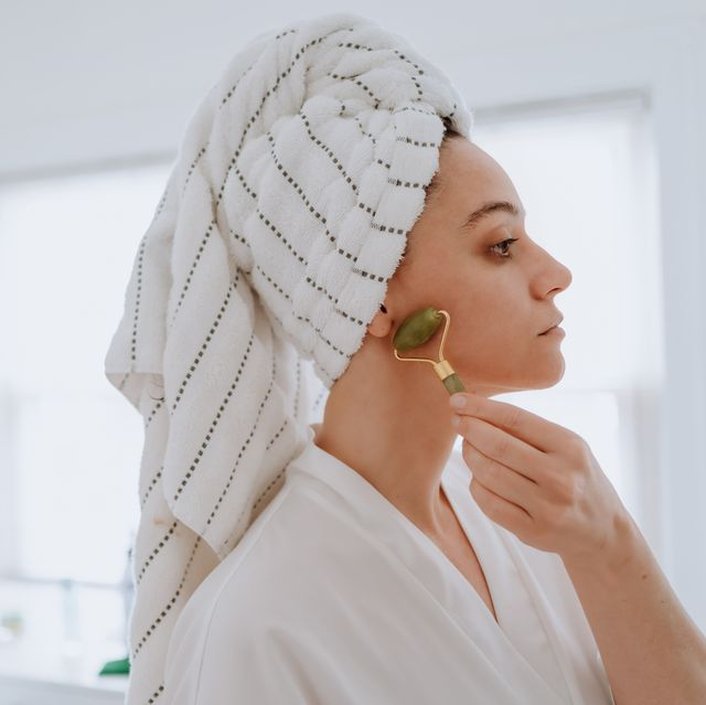 woman using jade roller on her face at home