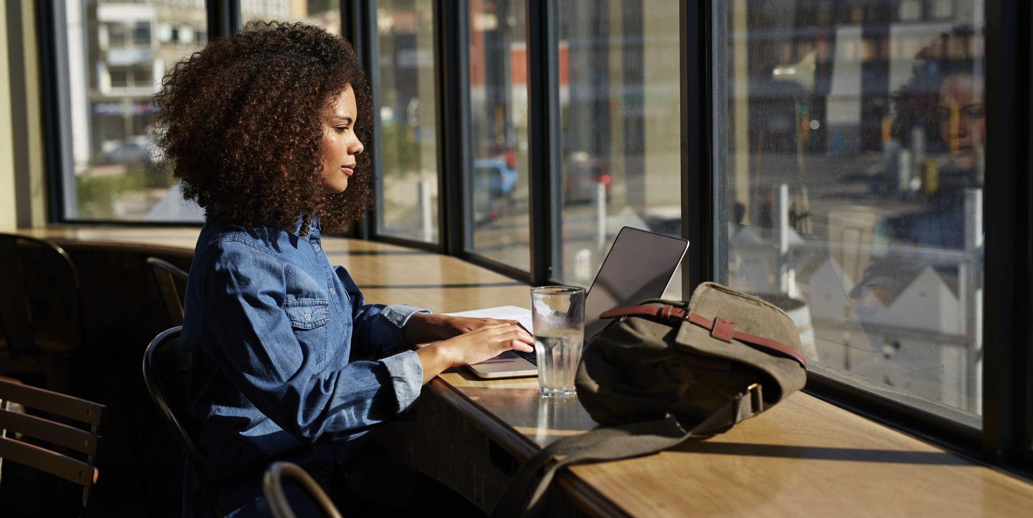 Woman using laptop at cafe at sunset