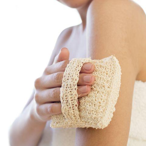 woman using loofah mitt on arm