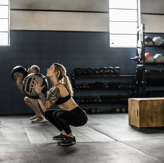 woman using medicine ball during exercise class