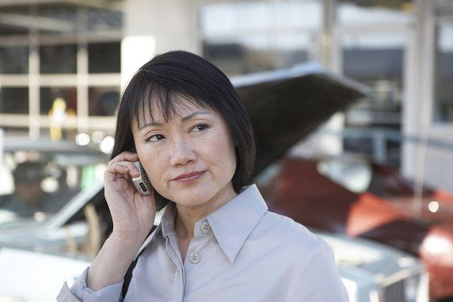 woman using mobile phone at car garage
