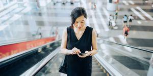 Woman using phone on an escalator