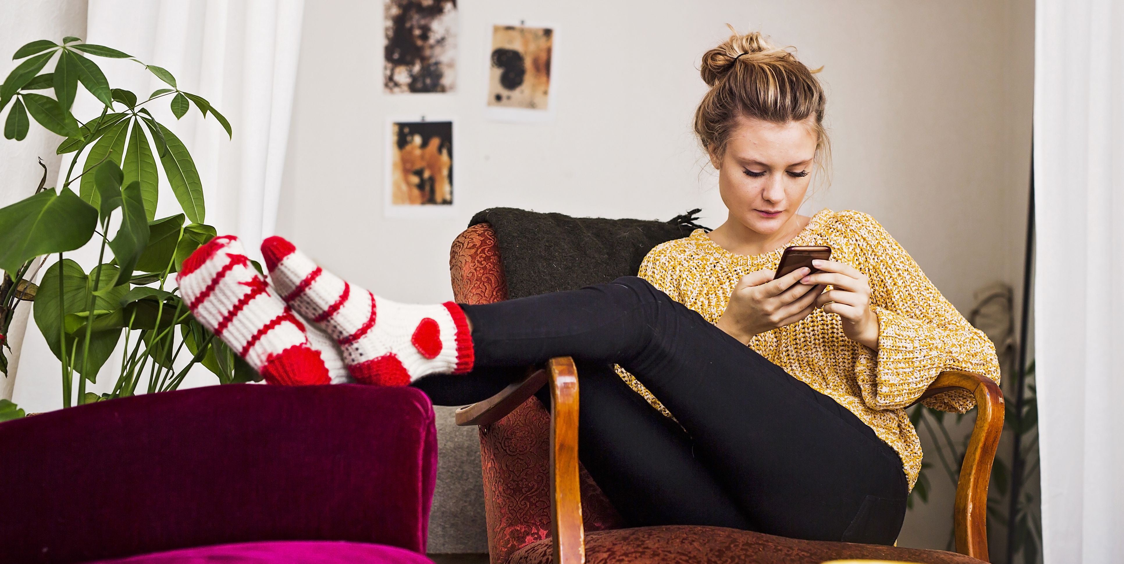 Woman using phone while resting on chair at home