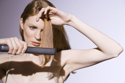 Woman using straight-iron on her hair